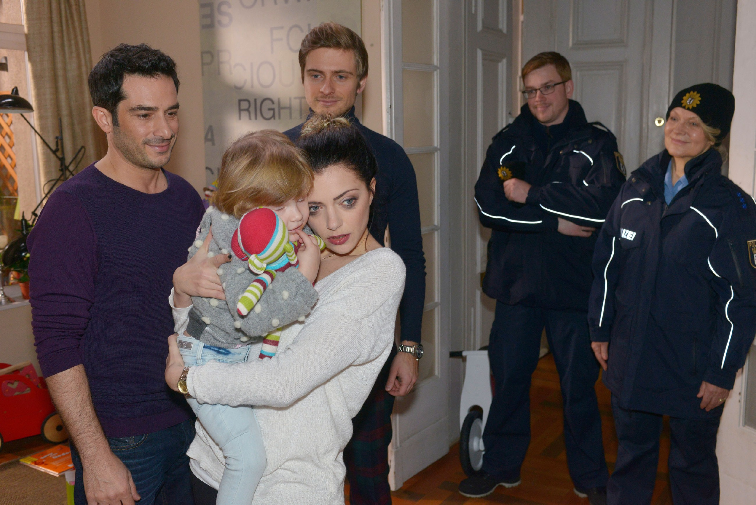 Tayfun (Tayfun Baydar, l.), Philip (Jörn Schlönvoigt, 2.v.l.) und Emily (Anne Menden) sind heilfroh, dass Kate unversehrt von der Polizei (Komparsen) gefunden wurde. (Quelle: RTL / Rolf Baumgartner)
