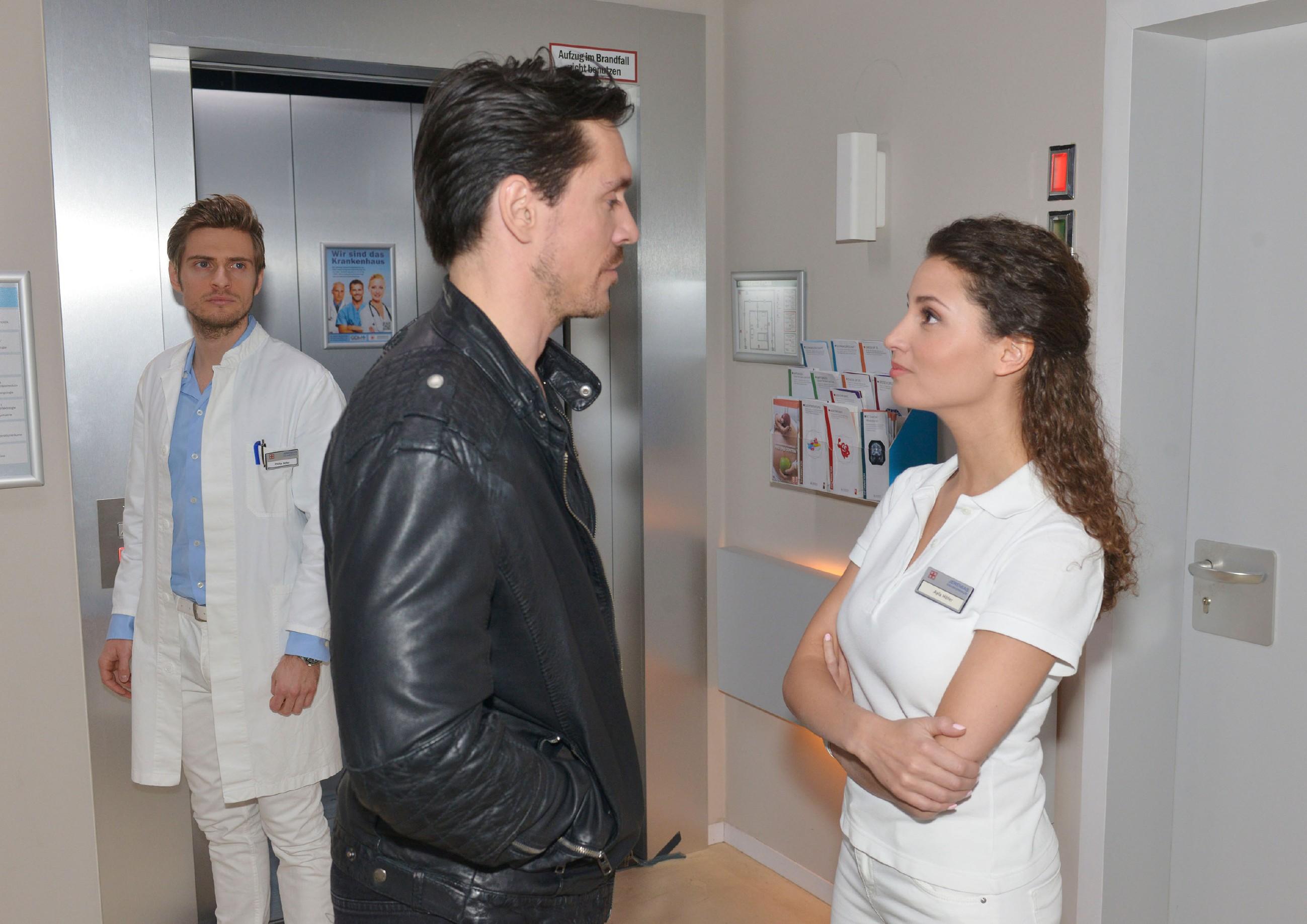 Als David (Philipp Christopher, M.) wegen Schmerzen im Knie überraschend im Krankenhaus aufschlägt, zeigt Ayla (Nadine Menz) ihm die kalte Schulter und lässt ihn ihre Enttäuschung spüren. Philip (Jörn Schlönvoigt) hingegen fragt sich, ob zwischen den beiden etwas läuft. (Quelle: RTL / Rolf Baumgartner)