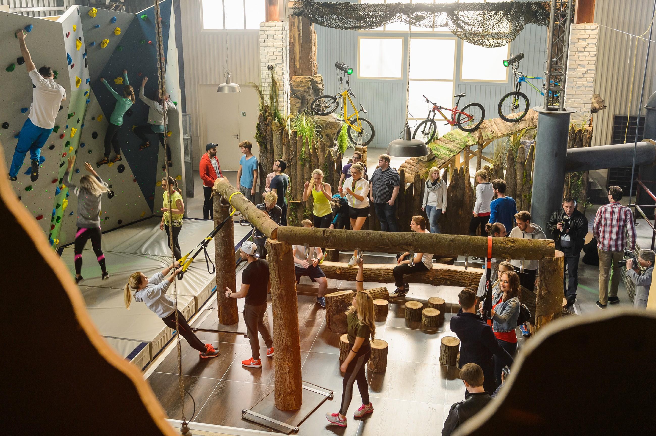 """Stolz eröffnet Deniz das Pumpwerk und stellt dem Publikum die Einrichtung und das Konzept """"Fitness ohne Maschinen"""" vor. (Quelle: RTL / Willi Weber)"""