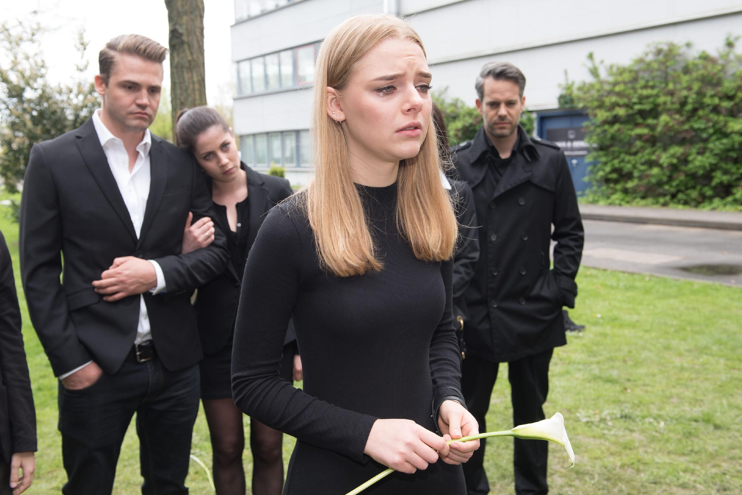 Als Fiona (Olivia Burkhart) ihren Vater im Kreise der Familie zu Grabe trägt, stehen Bambi (Benjamin Heinrich, l.), Sina (Valea Katharina Scalabrino) und Till (Ben Ruedinger) ihr bei. (Quelle: RTL / Stefan Behrens)