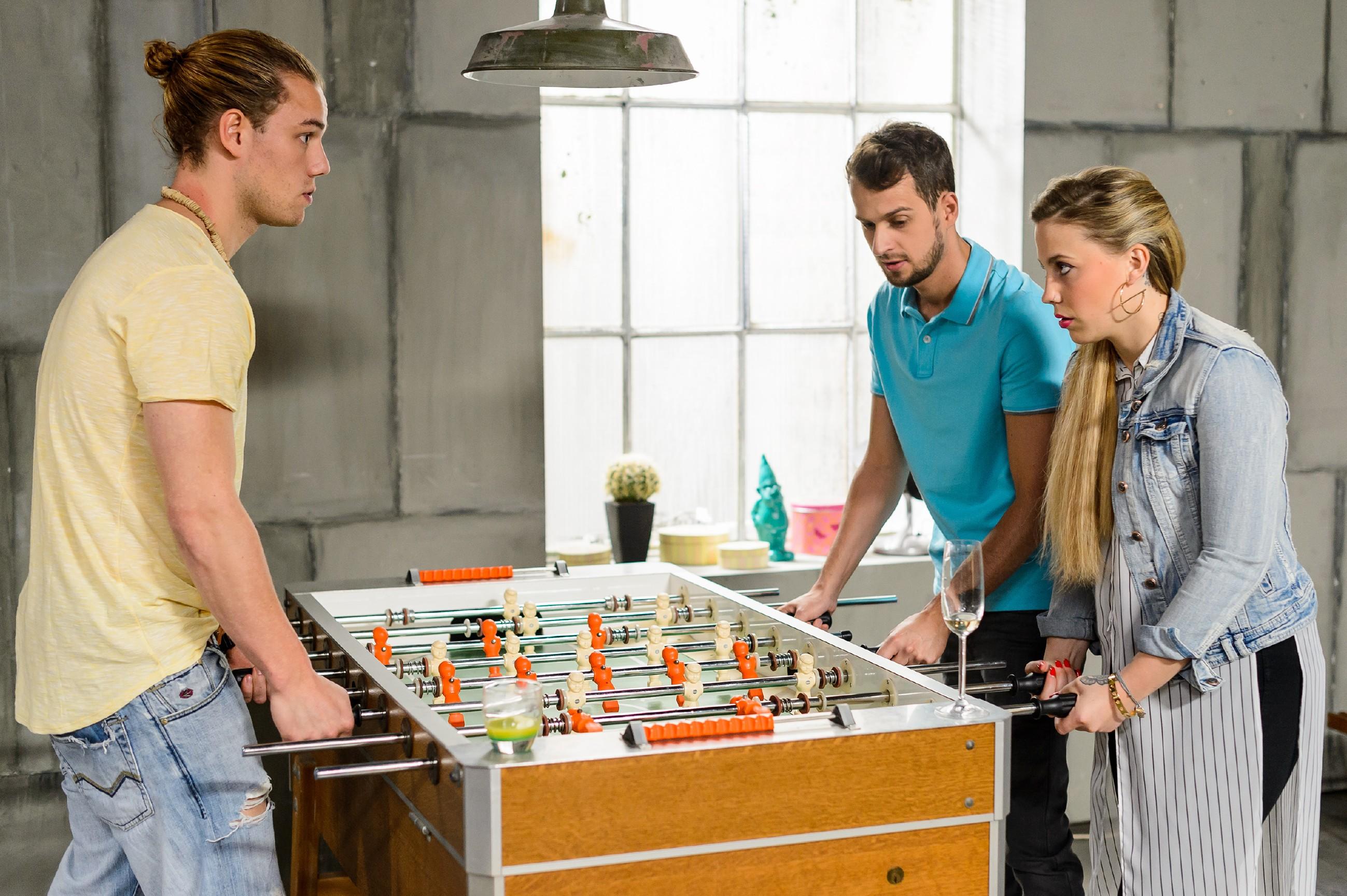 Als Iva (Christina Klein) mit Leo (Julian Bayer, l.) und Tobi (Michael Jassin) eine Runde Kicker spielt, wird ihr klar, dass Leo seinen Konkurrenten in Bezug auf Marie mit Alkohol ausgeschaltet hat. (Quelle: RTL / Willi Weber)