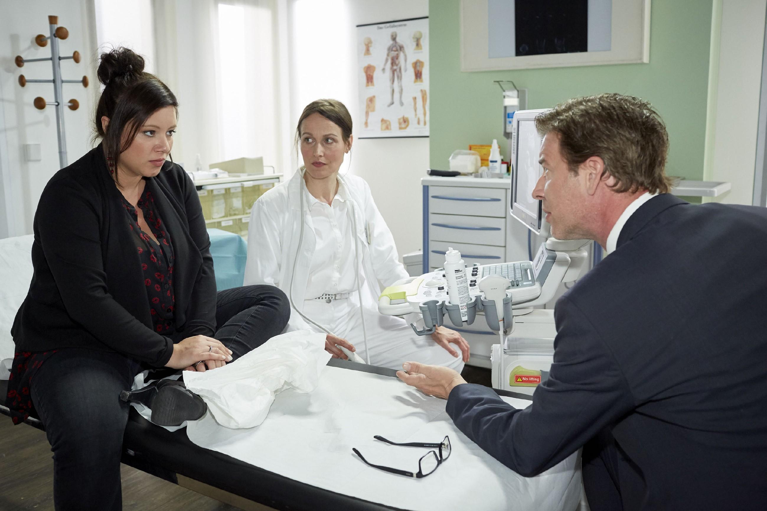 Vanessas (Julia Augustin, l.) und Christophs (Lars Korten) Euphorie erhält einen Dämpfer, als sie bei der Untersuchung von Dr. Fink (Barbara Seifert erfahren, dass mit ihrem Baby vielleicht etwas nicht in Ordnung ist. (Quelle: RTL / Guido Engels)
