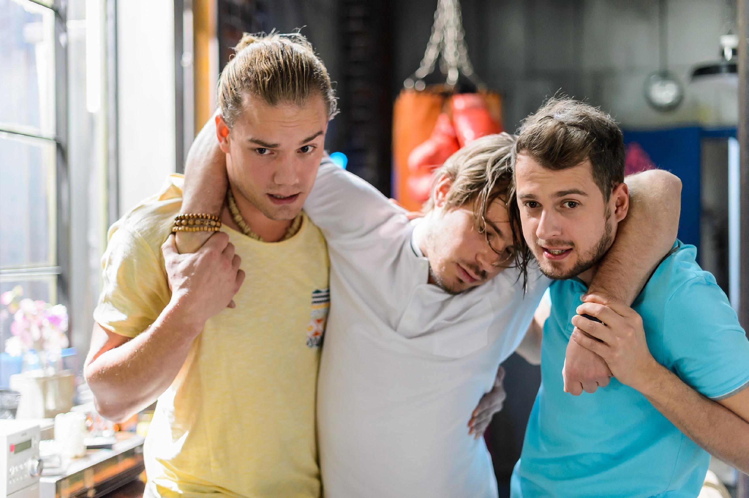 Leo (Julian Bayer, l.) und Tobi (Michael Jassin, r.) kümmern sich um Sam (Alexander Milz), der von Leo abgefüllt wurde, damit er nicht mit Marie flirten kann.