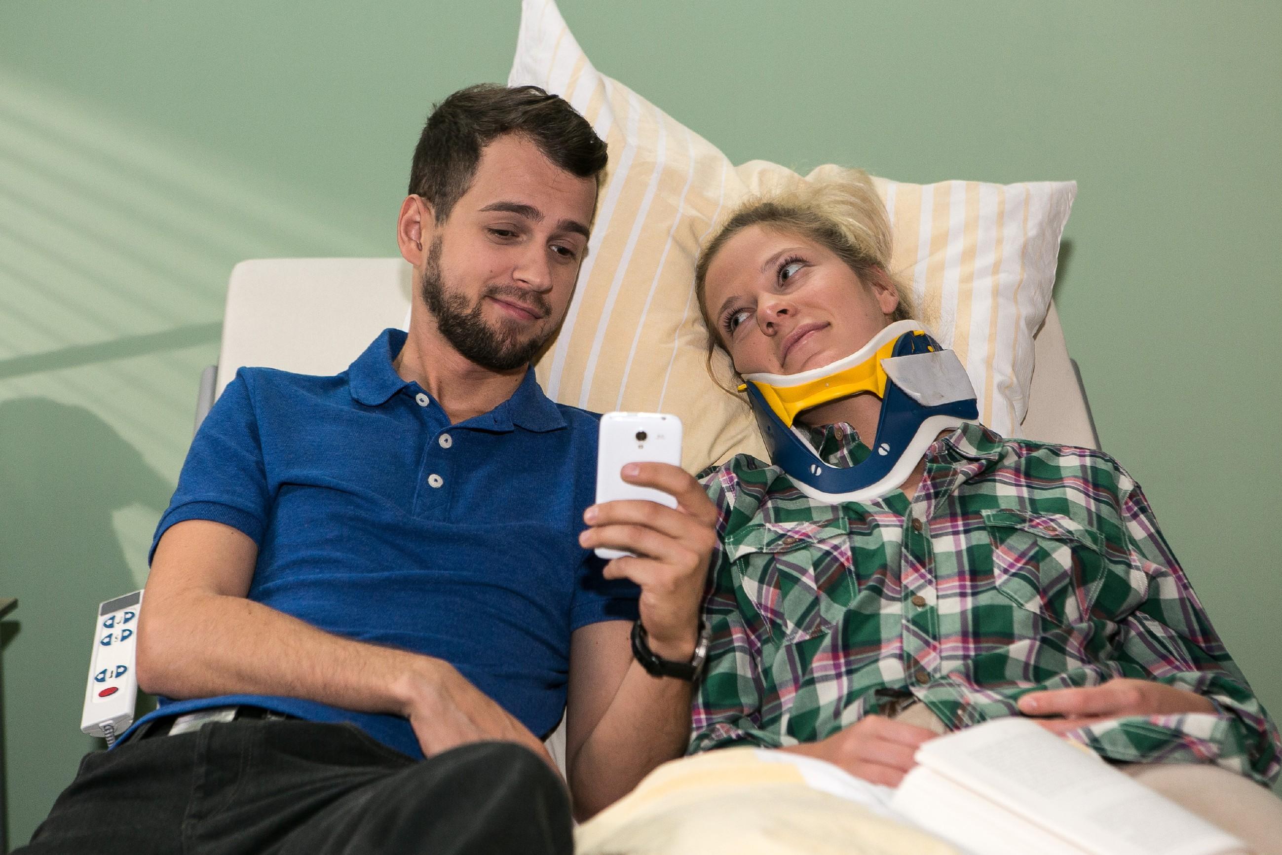 Tobi (Michael Jassin) liest Marie (Cheyenne Pahde) Witze vom Handy vor, um sie von ihrer Misere abzulenken. (Quelle: RTL / Kai Schulz)