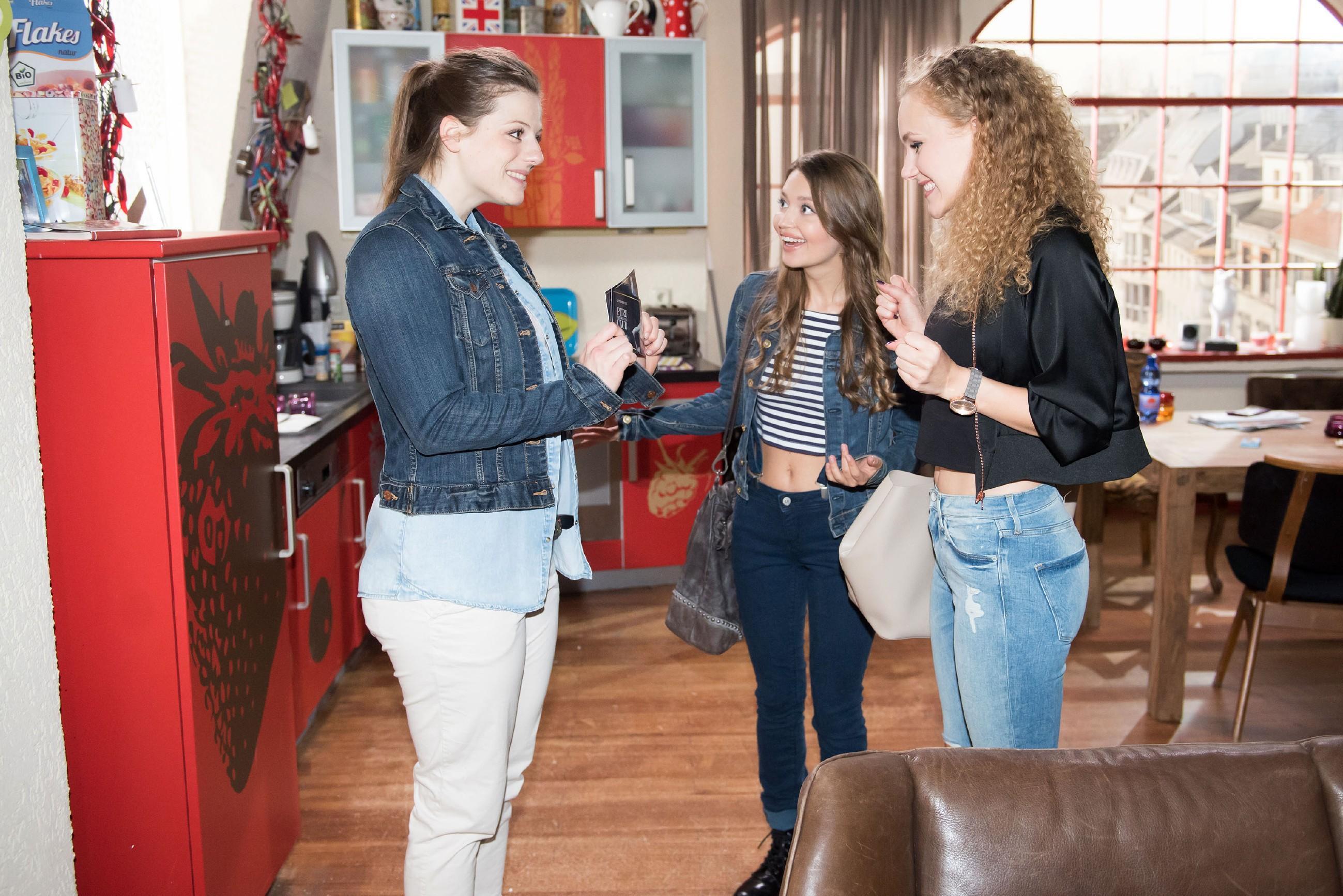 Elli (Nora Koppen, l.) übergibt KayC (Pauline Angert, r.) im Beisein von Jule (Amrei Haardt) die Karten für einen gemeinsamen Abend und ist glücklich, als KayC begeistert reagiert.