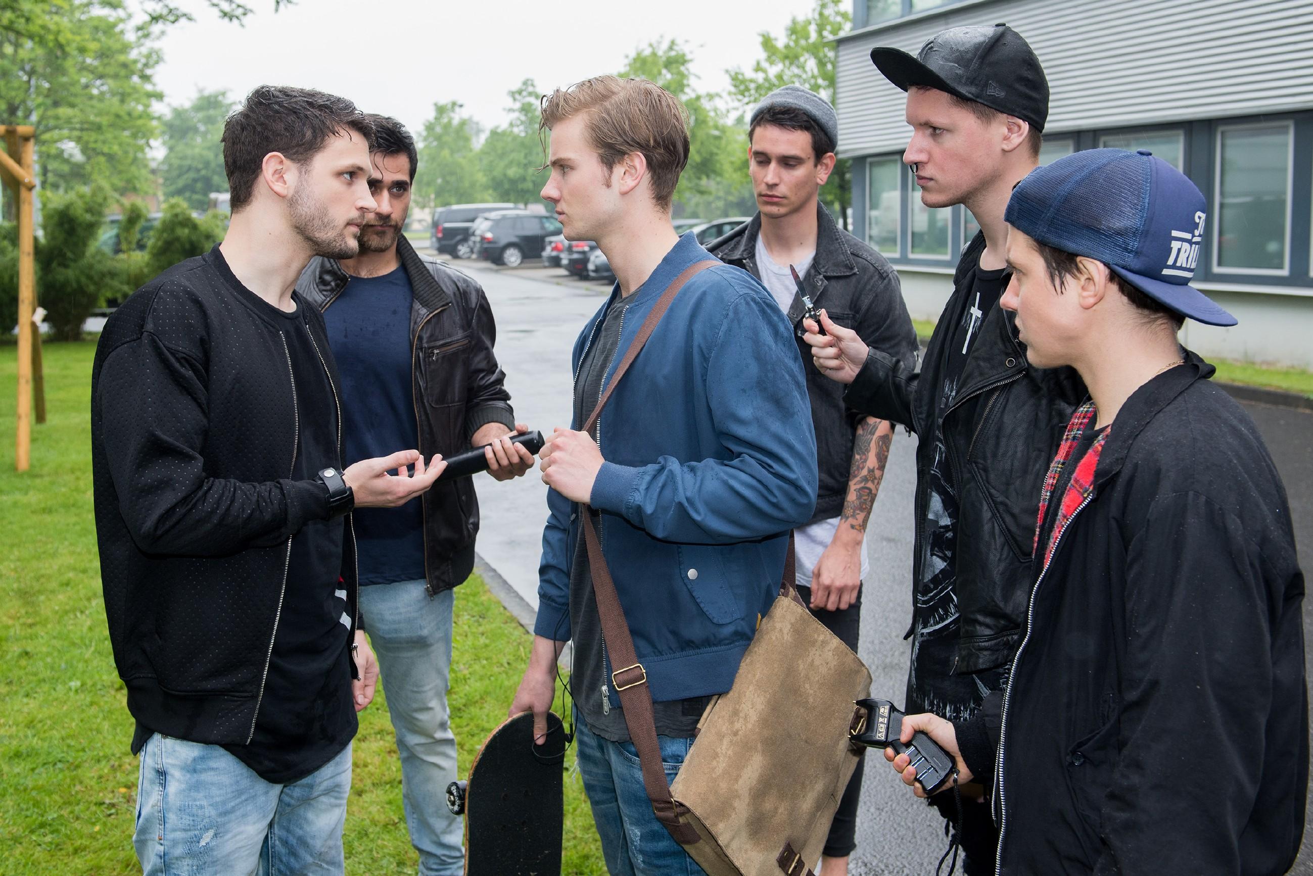 Valentin (Aaron Koszuta, M.) wird von Mario (Arne Rudolf, l.) und seinen gewaltbereiten Gangmitgliedern (Komparsen) bedrängt.