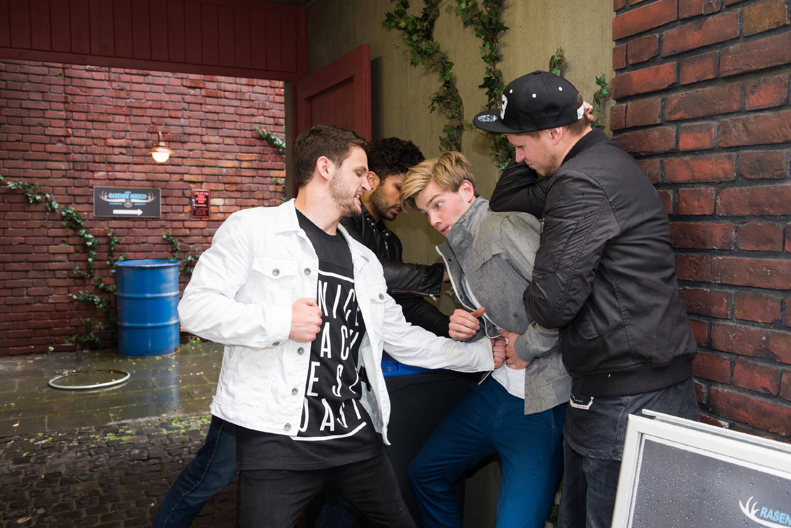 Valentin (Aaron Koszuta, 2.v.r.) tritt in seinem Demütigungs-Frust die schmerzvolle Flucht nach vorn an und provoziert eine nicht zu gewinnende Prügelei mit Mario (Arne Rudolf, l.) und seiner Gang (Komparsen).