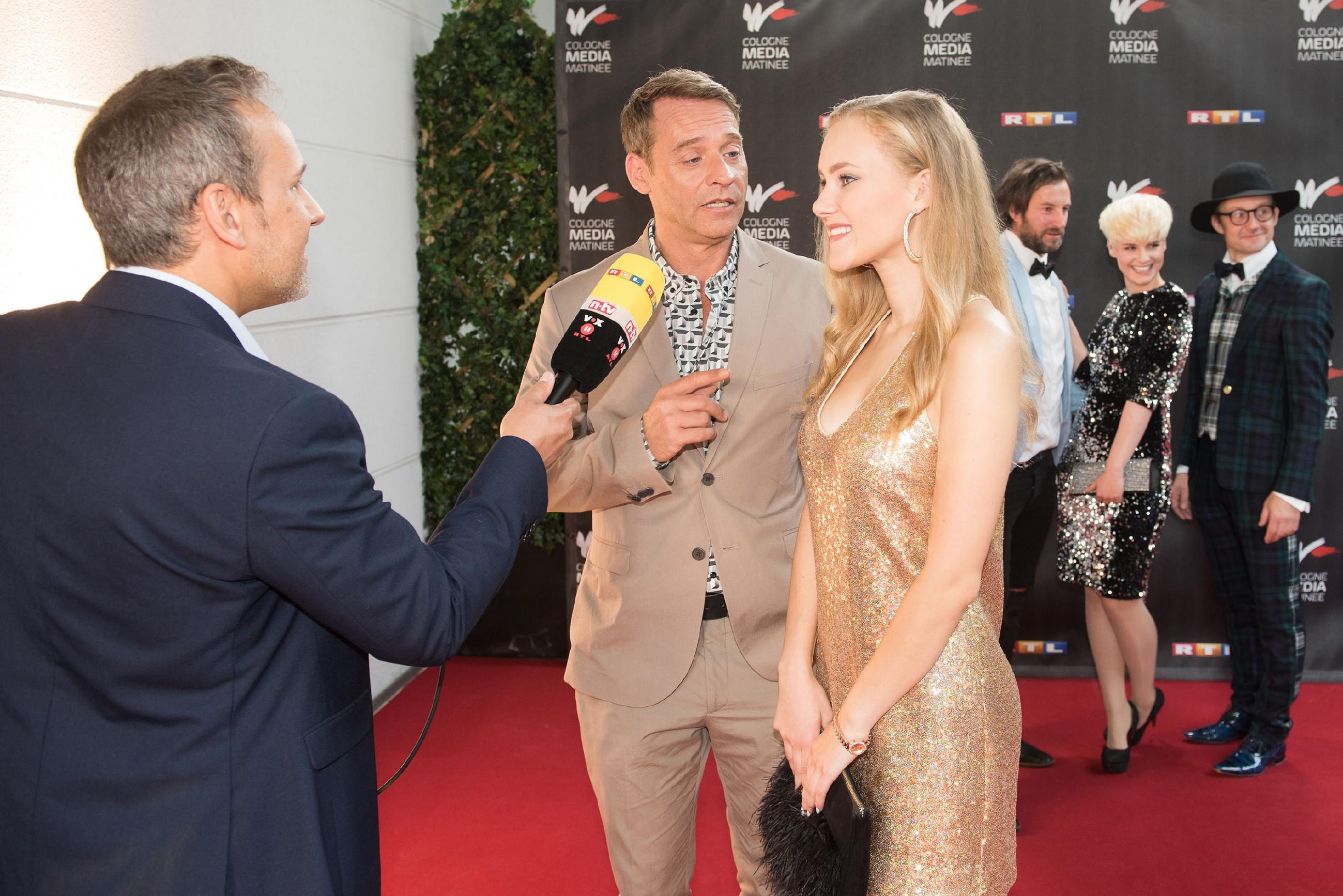 KayC (Pauline Angert) überrascht Rufus (Kai Noll, M.), indem sie plötzlich bei dem Promi-Event gutgelaunt neben ihm auf dem roten Teppich steht... (l. Komparse)(Quelle: RTL / Stefan Behrens)