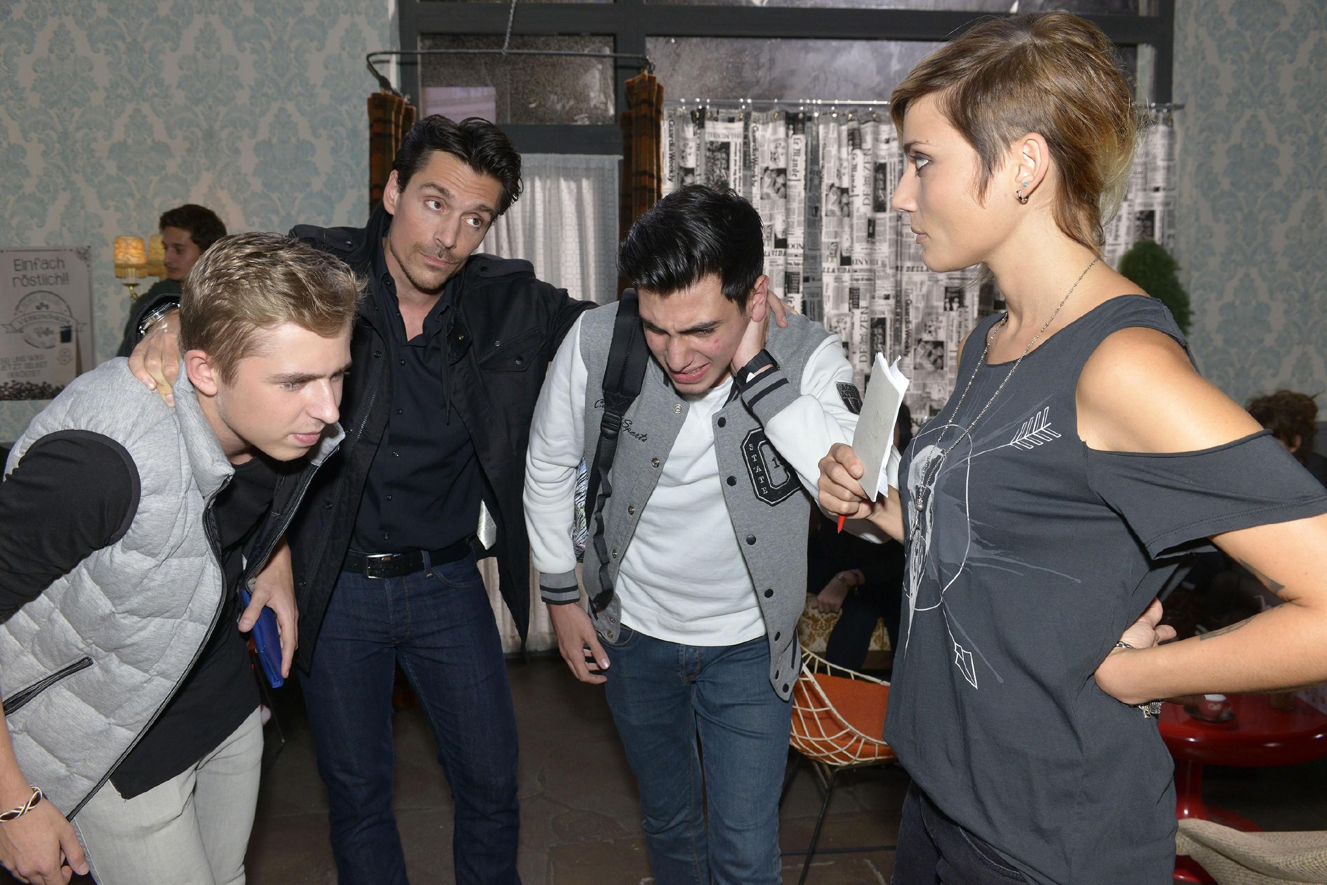 Obwohl David (Philipp Christopher, 2.v.l.) Anni (Linda Marlen Runge, r.) bei einer stressigen Schicht mit nervenden Gästen (Komparsen) im Vereinsheim hilft, ist sie nicht bereit, ihm zu verzeihen. (Quelle: RTL / Rolf Baumgartner)