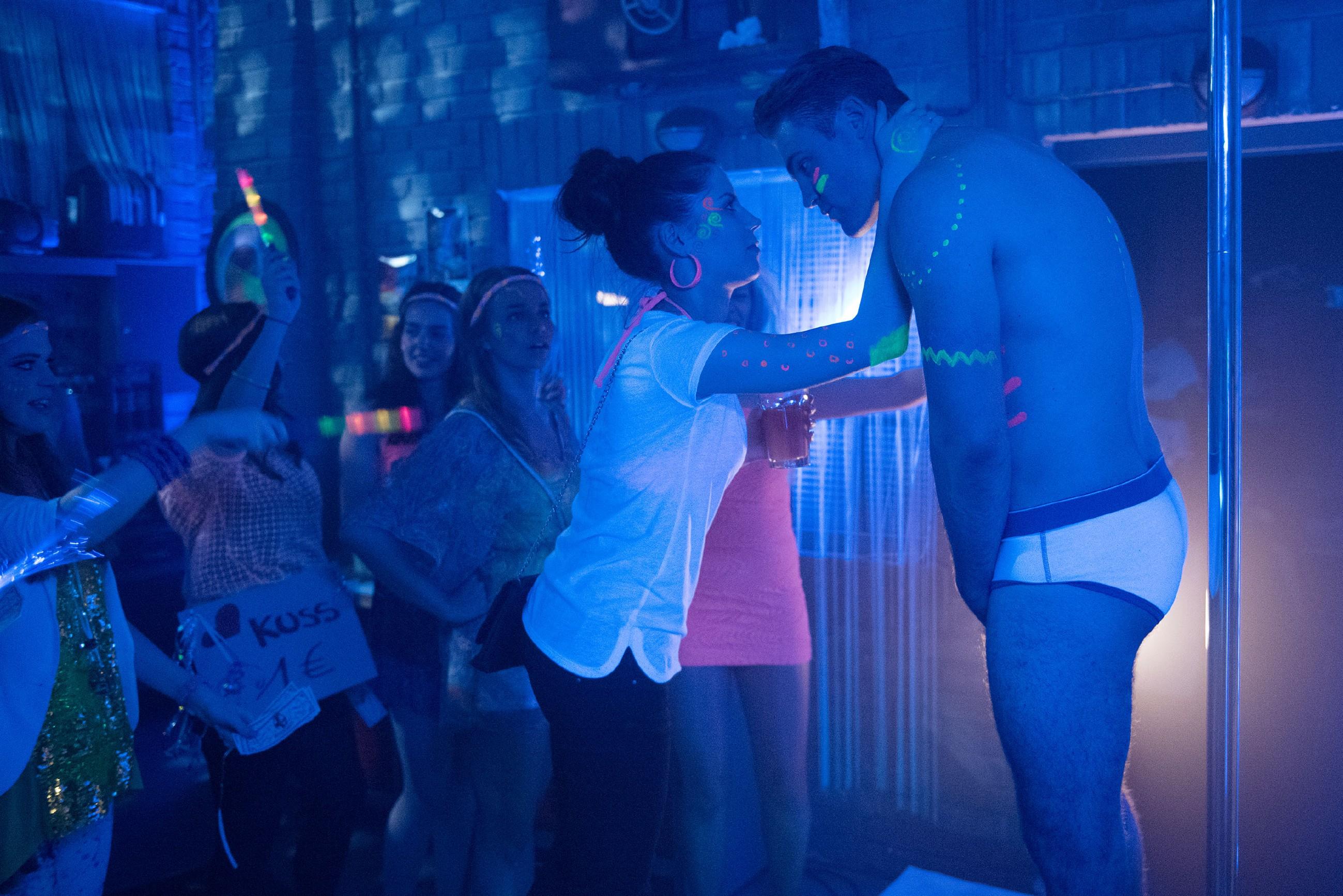 Bambi (Benjamin Heinrich) ist erleichtert, dass Sina (Valea Katharina Scalabrino) seine spontane Striptease-Einlage bei der Werkstattparty offenbar locker sieht. (Quelle: RTL / Stefan Behrens)