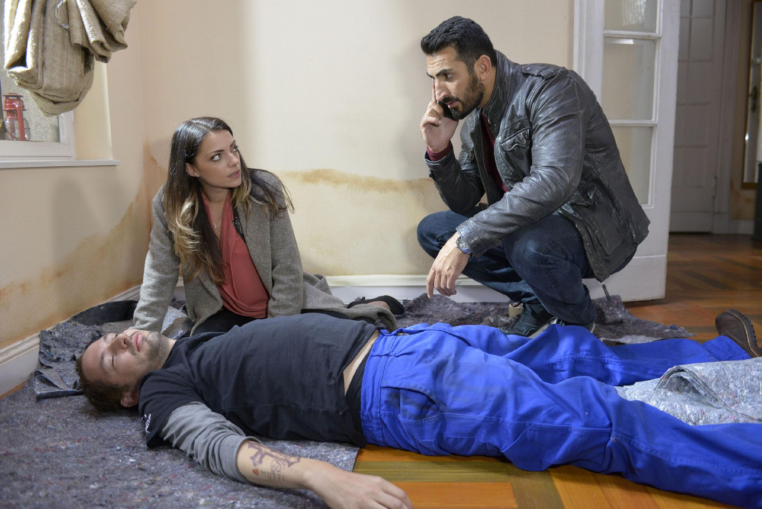 Emily (Anne Menden) und Mesut (Mustafa Alin, r.) sind schockiert, als der Handwerker Maik Wollnitz (Ulrich Faßnacht) bewusstlos in der Wohnung liegt. (Quelle: RTL / Rolf Baumgartner)