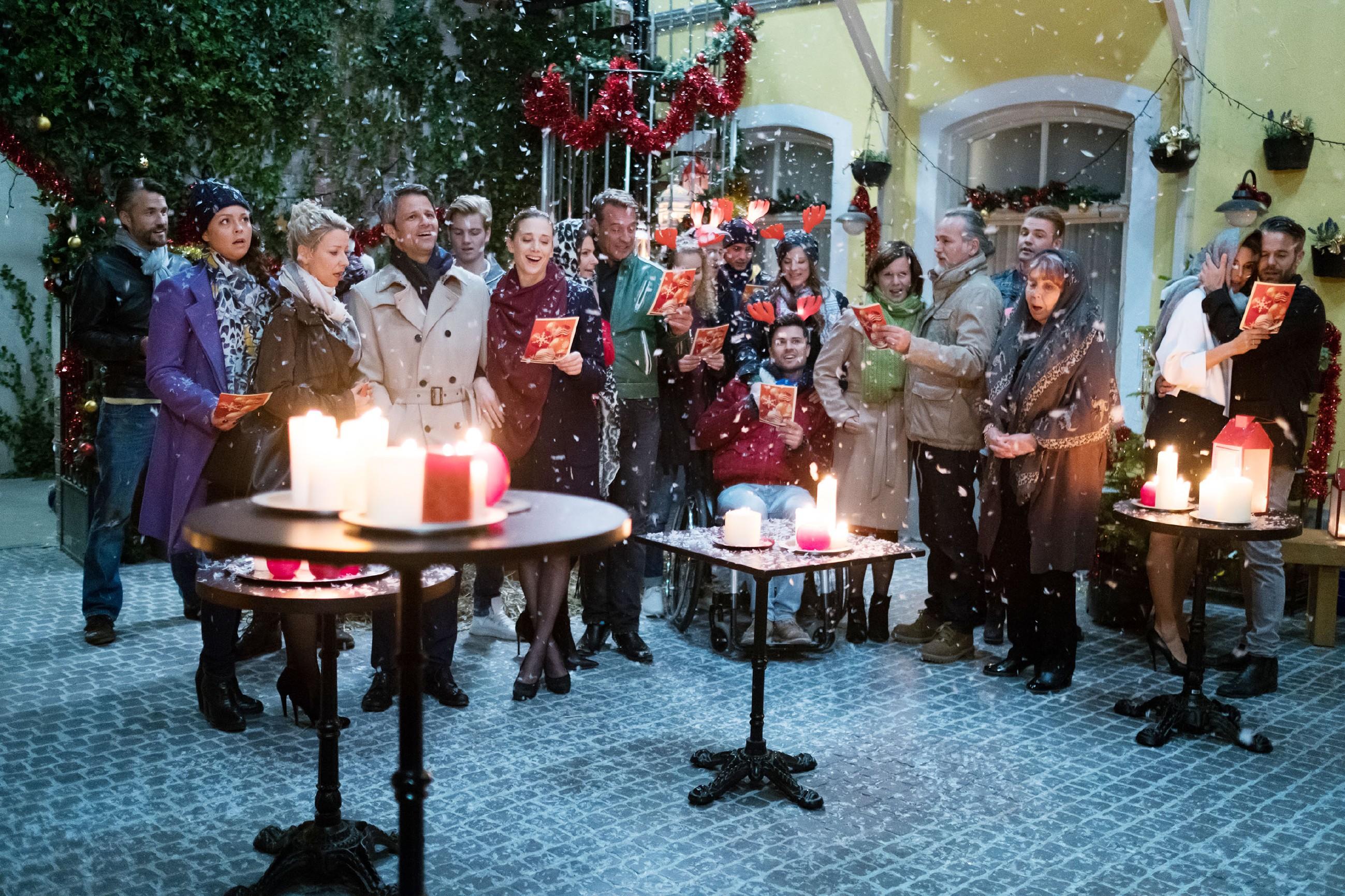 Traditionell haben sich die Bewohner der Schillerallee, v.l.) Malte (Stefan Bockelmann), Caro (Ines Kurenbach), Ute (Isabell Hertel), Benedikt (Jens Hajek), Valentin (Aaron Koszuta), Andrea (Kristin Meyer), Britta (Tabea Heynig), Rufus (Kai Noll), KayC (Pauline Angert), Ringo (Timothy Boldt), Paco (Milos Vukovic), Elli (Nora Koppen), Irene (Petra Blossey), Robert (Luca Maric), Bambi (Benjamin Heinrich), Roswitha (Andrea Brix), Eva (Claudelle Deckert) und Till (Ben Ruedinger), im Innenhof zum gemeinsamen Singen eingefunden. (Quelle: RTL / Stefan Behrens)