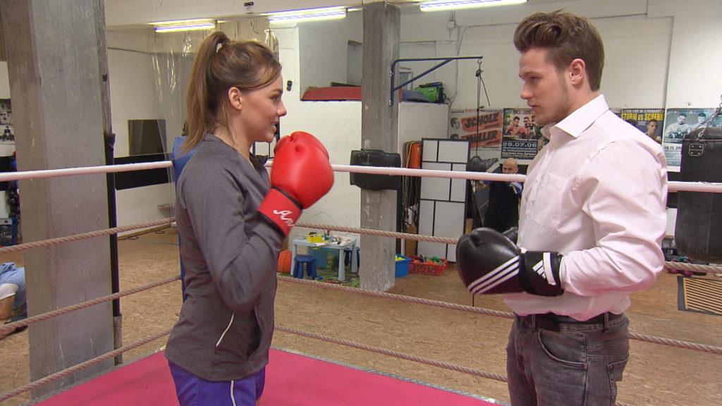Valentin,re., macht sich über Annas,li., Karrierepläne als Kickboxtrainerin lustig und verärgert seine Freundin damit sehr.