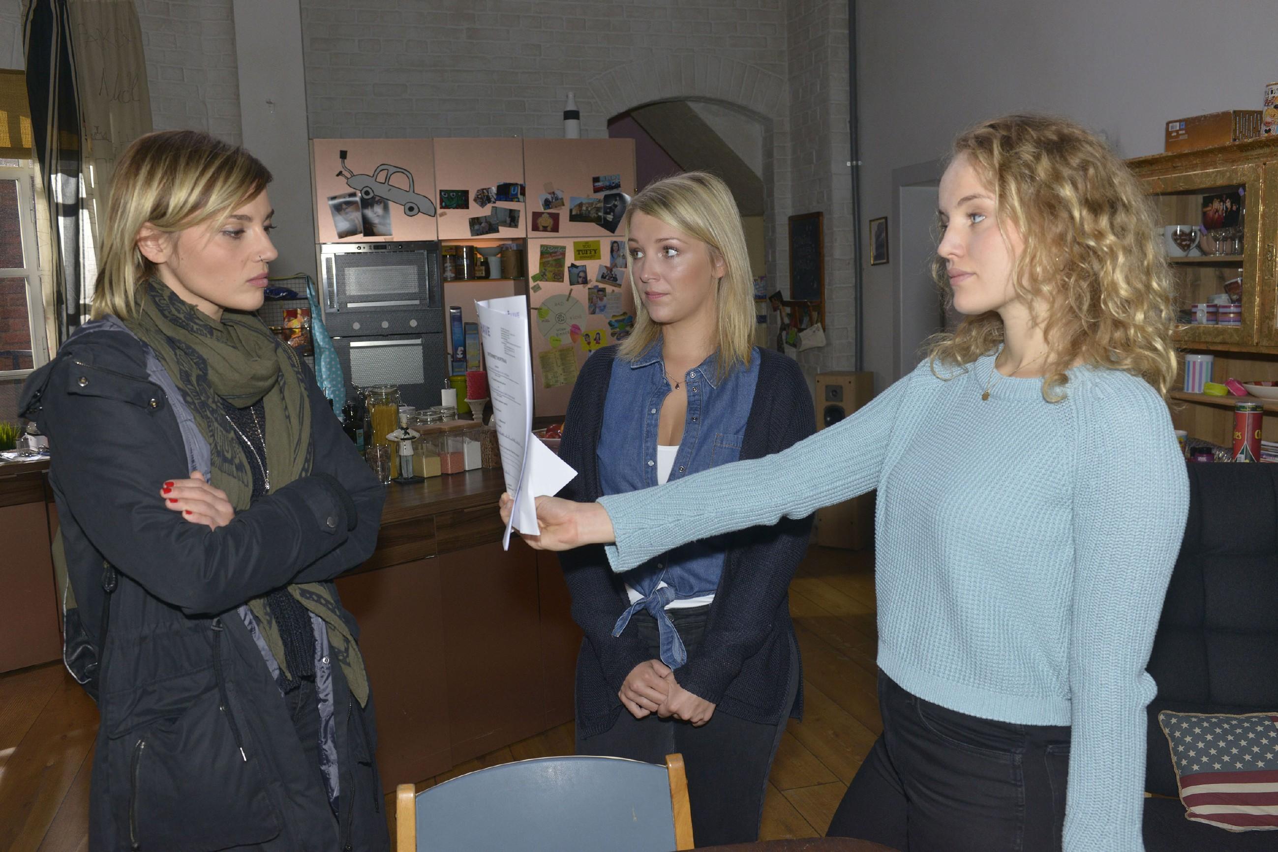 Anni (Linda Marlen Runge, l.) ist fassungslos, als ihre Halbschwester Jule (Luise von Finckh, r.) ihr einen Mietvertrag für die WG präsentiert, den sie von Lilly (Iris Mareike Steen) bekommen hat. (Quelle: RTL / Rolf Baumgartner)