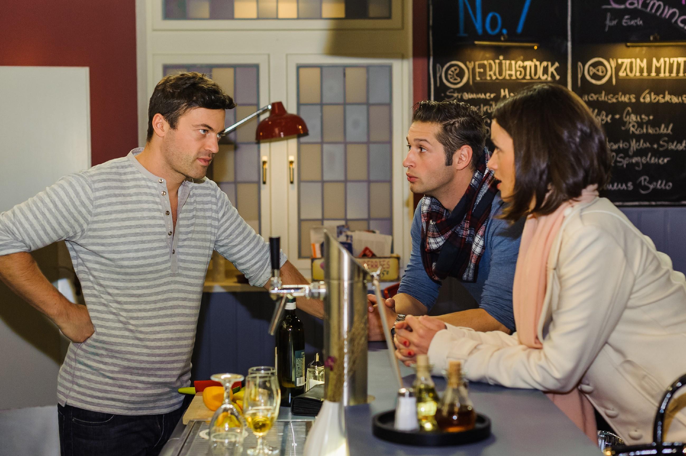 Jenny (Kaja Schmidt-Tychsen) und Deniz (Igor Dolgatschew) stehen bei Ben (Jörg Rohde) an der Theke und befürchten, dass sie mit ihrer Erpressung nicht durchkommen. (Quelle: RTL / Julia Feldhagen)