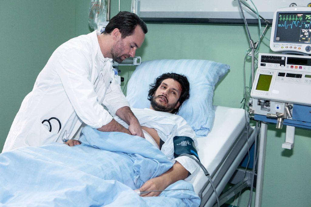 Maximilian (Francisco Medina, r.) wird von Thomas (Daniel Brockhaus) untersucht und erkennt seine aussichtslose Lage.