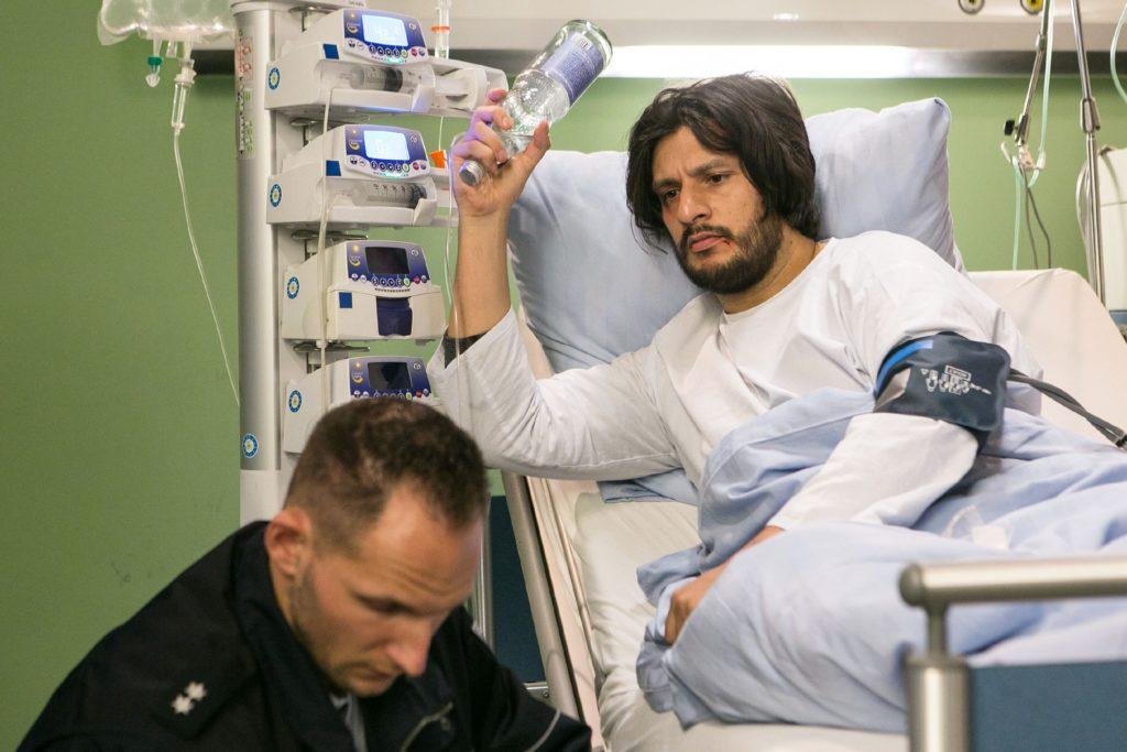 Maximilian (Francisco Medina, r.) schlägt im Krankenzimmer einen Sicherheitsbeamten (Komparse) nieder, um die Flucht aus dem Krankenzimmer zu wagen...