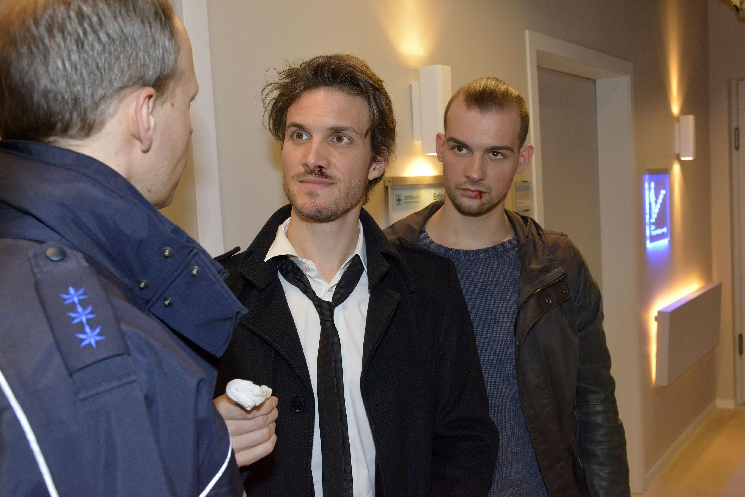 Felix (Thaddäus Meilinger, M.) stellt sich vor seinen Bruder und belügt den Polizisten (l. Komparse), um Chris (Eric Stehfest, r.) zu schützen. (Quelle: RTL / Rolf Baumgartner)