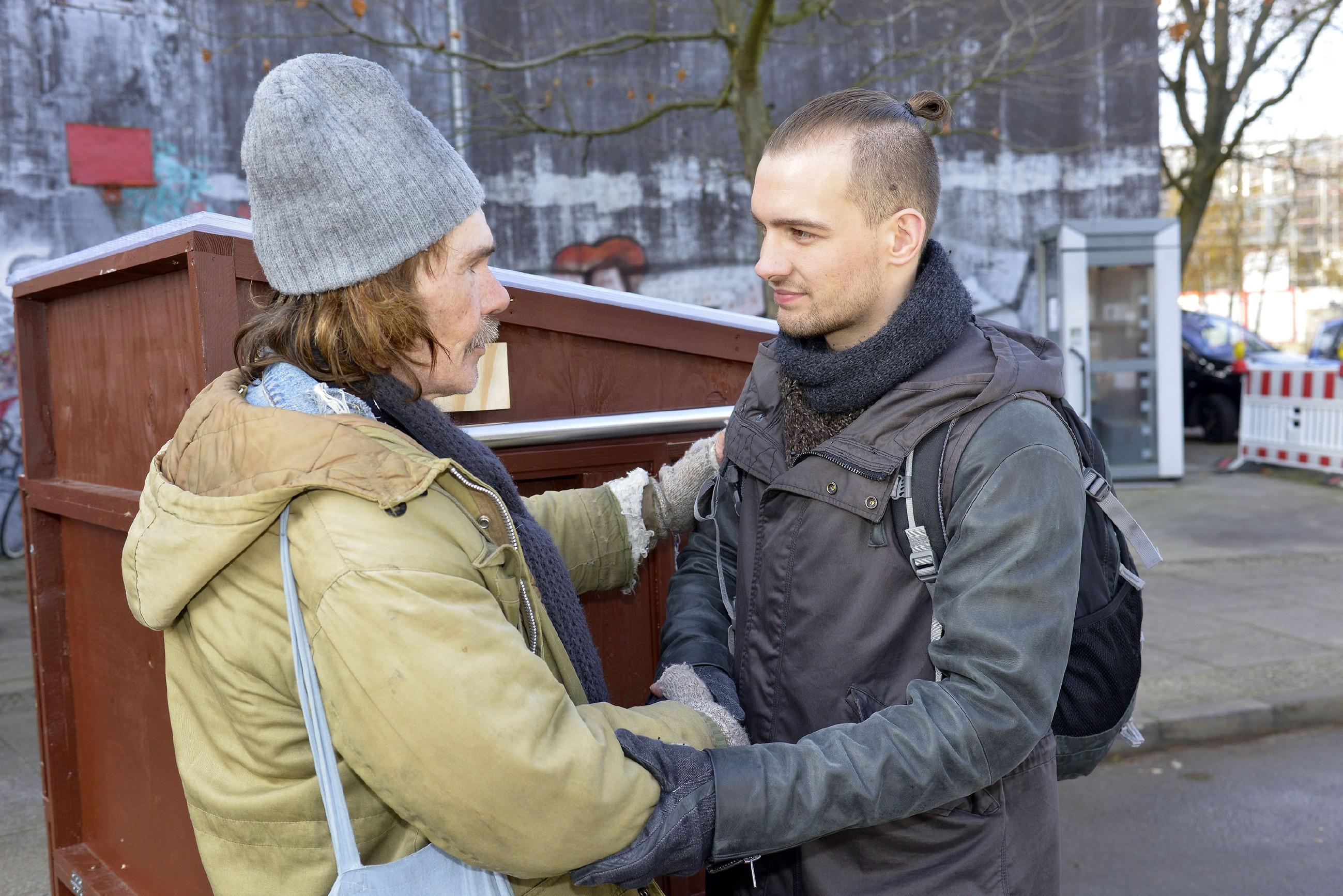 """Chris (Eric Stehfest, r.) freut sich, die ersten """"Tiny Huts"""" an die Obdachlosen (l. Komparse) weitergeben zu können. (Quelle: RTL / Rolf Baumgartner)"""