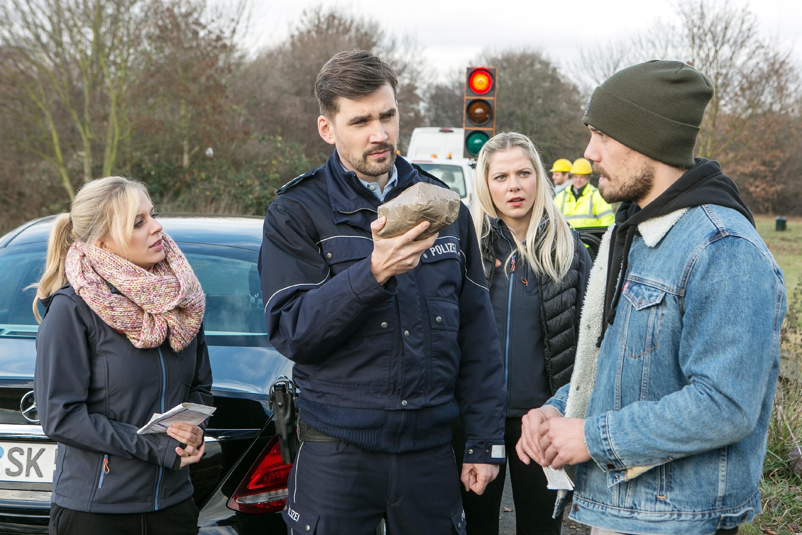 Leo (Julian Bayer, r.) ist entsetzt, als der Polizist Schlömann (Jochen Alexander Wiegand) in Gegenwart von Lena (Juliette Greco, l.) und Marie (Cheyenne Pahde) einen überraschenden Fund in seinem Auto macht... (Quelle: RTL / Kai Schulz)