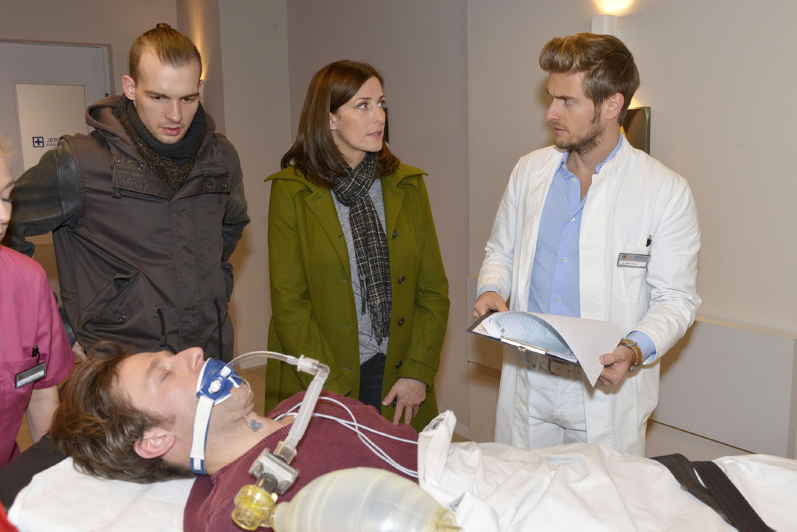 Chris (Eric Stehfest, l.) und Katrin (Ulrike Frank) begleiten Till (Merlin Leonhardt, vorne) nach seinem Zusammenbruch ins Krankenhaus und hoffen, dass Philip (Jörn Schlönvoigt) und die Ärzte ihm helfen können.