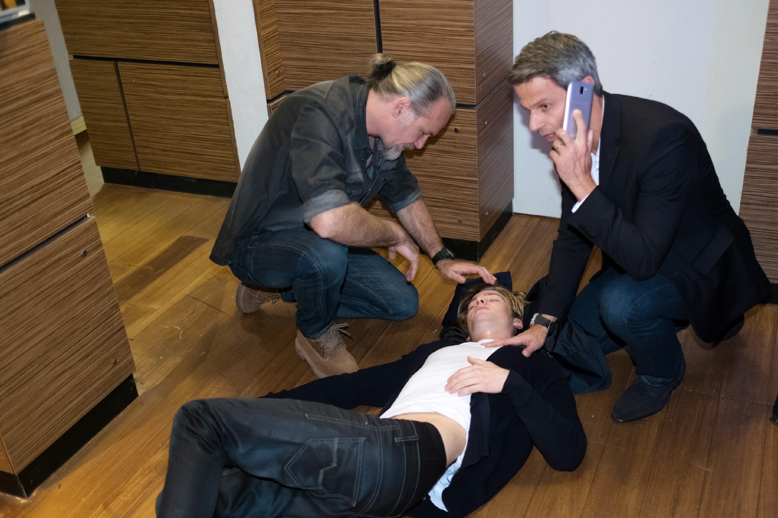 Robert (Luca Maric, l.) und Benedikt (Jens Hajek, r.) kümmern sich um den bewusstlosen Valentin (Aaron Koszuta) und rufen den Notarzt.