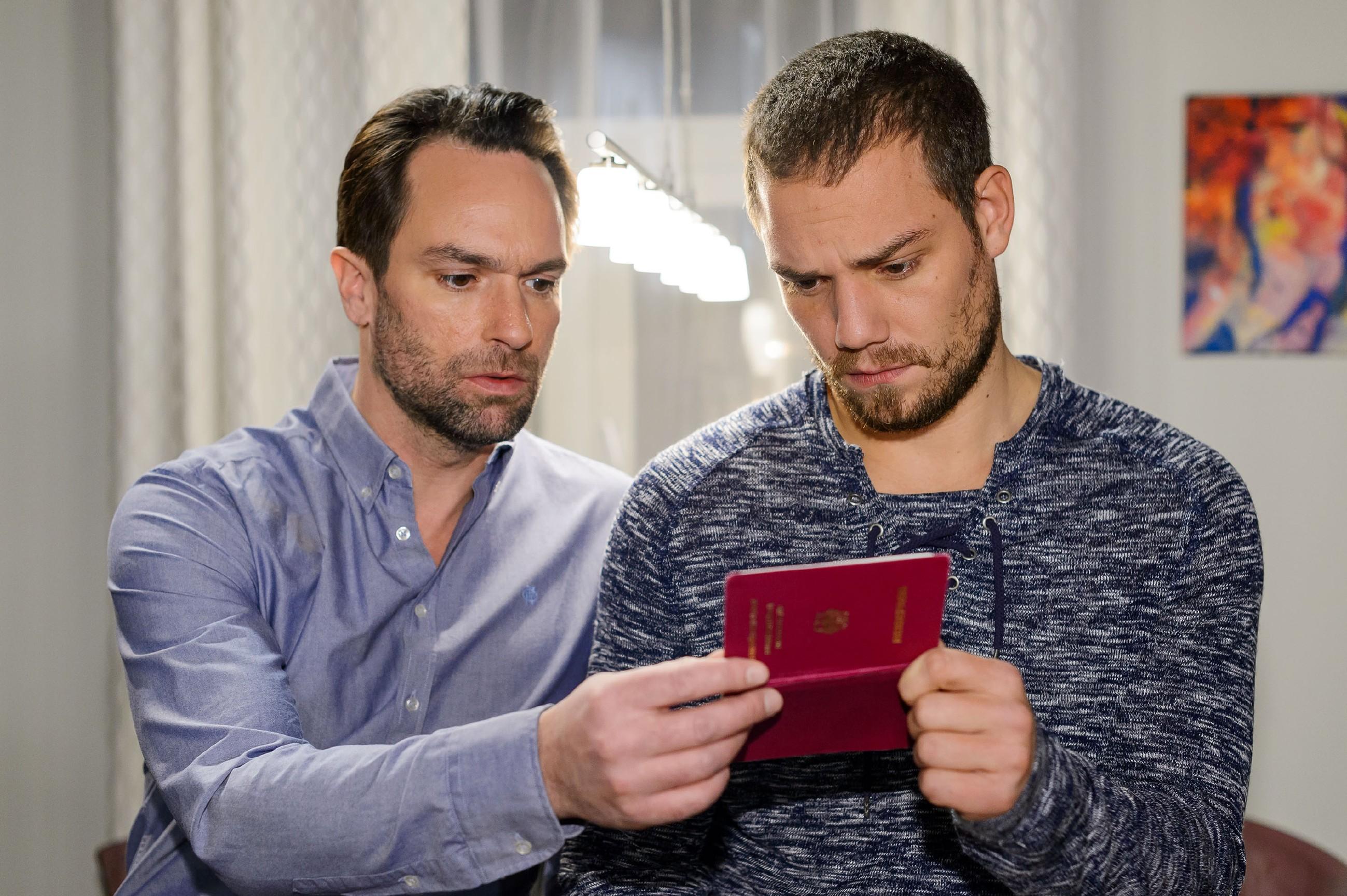 Thomas (Daniel Brockhaus, l.) und Leo (Julian Bayer) begutachten gemeinsam Leos gefälschten Pass. (Quelle: RTL / Willi Weber)