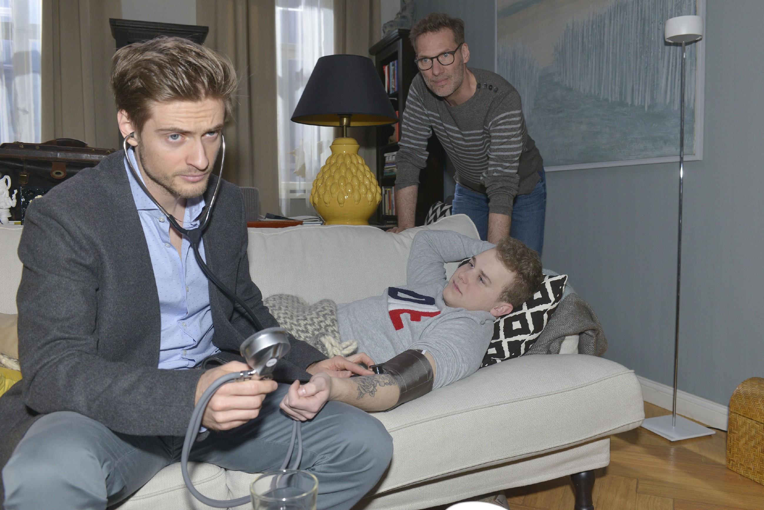 Während Philip (Jörn Schlönvoigt, l.) Jonas (Felix van Deventer, M.) untersucht, muss dieser sich vor Alexander (Clemens Löhr) eingestehen, dass er nicht ganz unschuldig an seinem Zusammenbruch ist. (Quelle: RTL / Rolf Baumgartner)