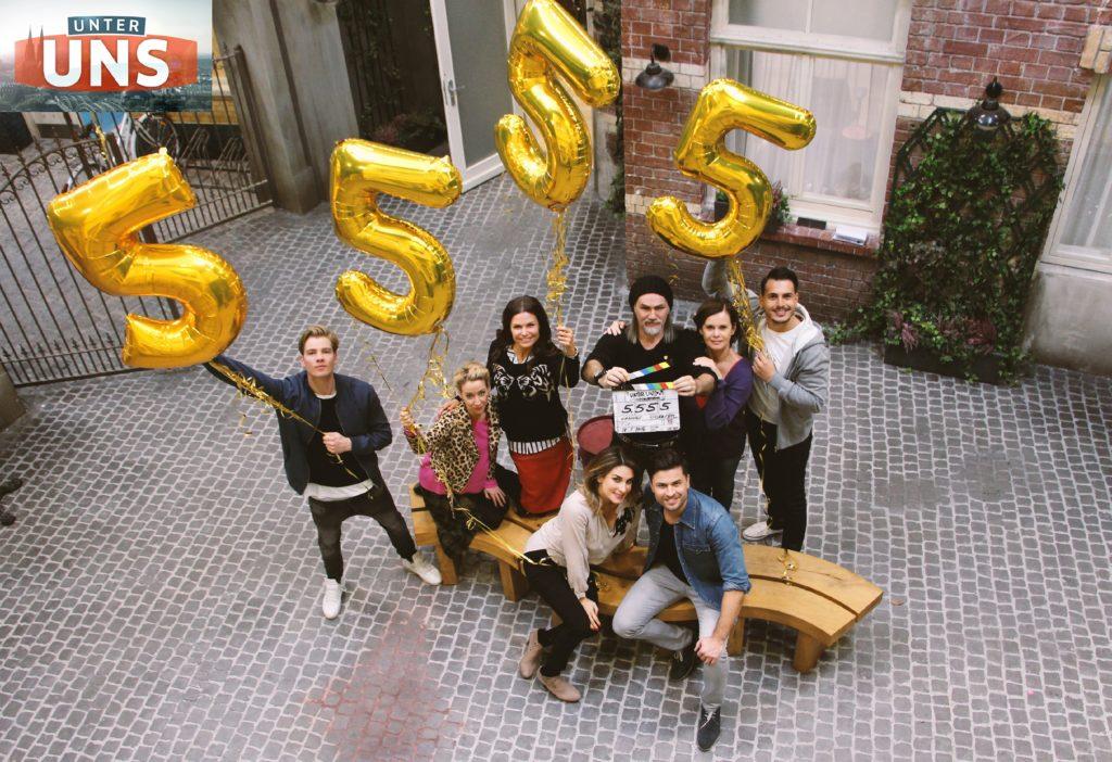 Die UNTER UNS-Schauspieler (stehend v.l.) Aaron Koszuta, Isabell Hertel, Tabea Heynig, Luca Maric, Petra Blossey, Cronis Karakassidis, (vorne) Claudelle Deckert und Milos Vukovic feiern die 5.555 Folge UNTER UNS.