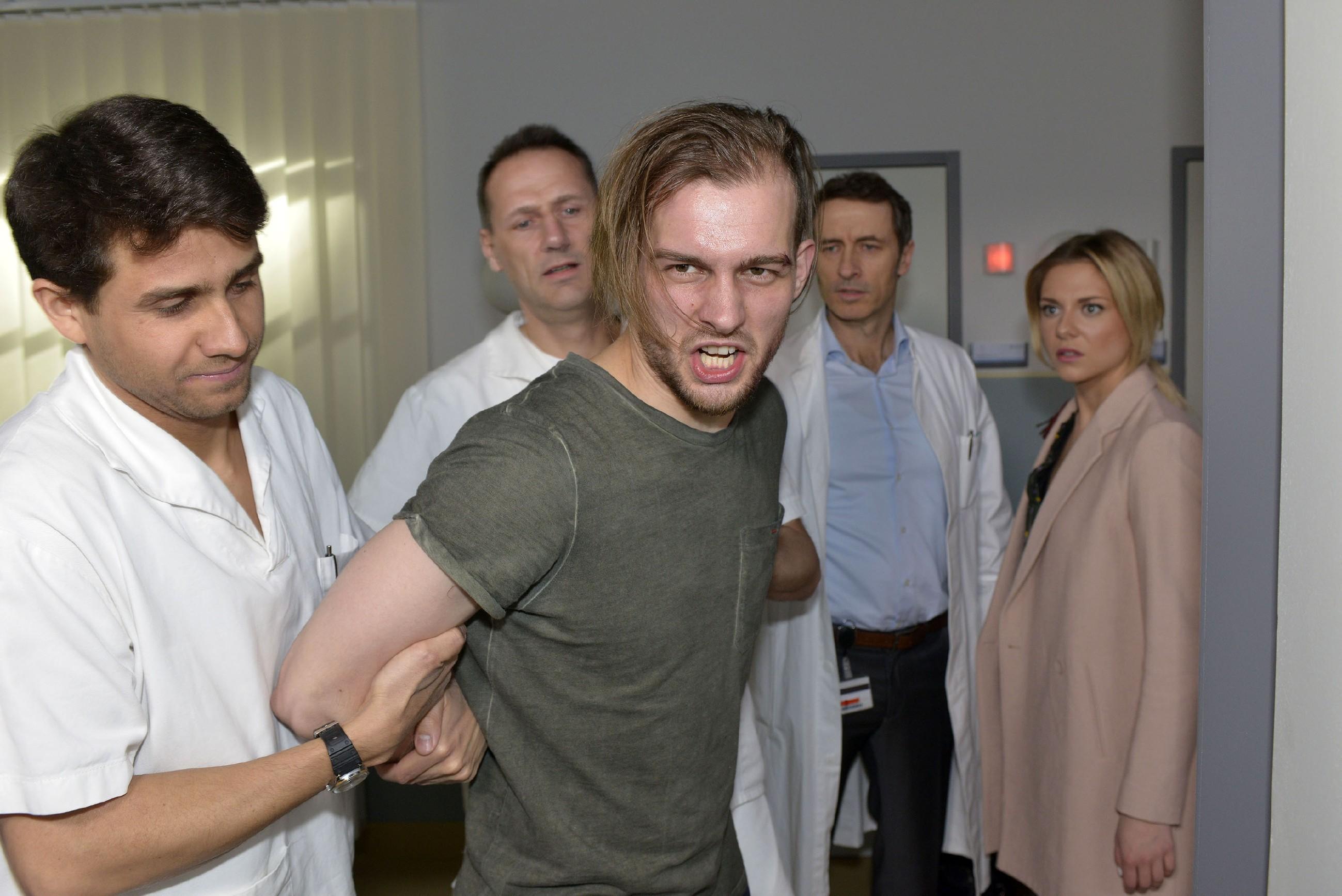Sunny (Valentina Pahde, r.) wird Zeugin, wie Chris (Eric Stehfest, M.) in der Psychiatrie von Dr. Wolf (Guido Broscheit, 2.v.r.) und zwei Pflegern (Komparsen) ruhiggestellt wird. (Quelle: RTL / Rolf Baumgartner)
