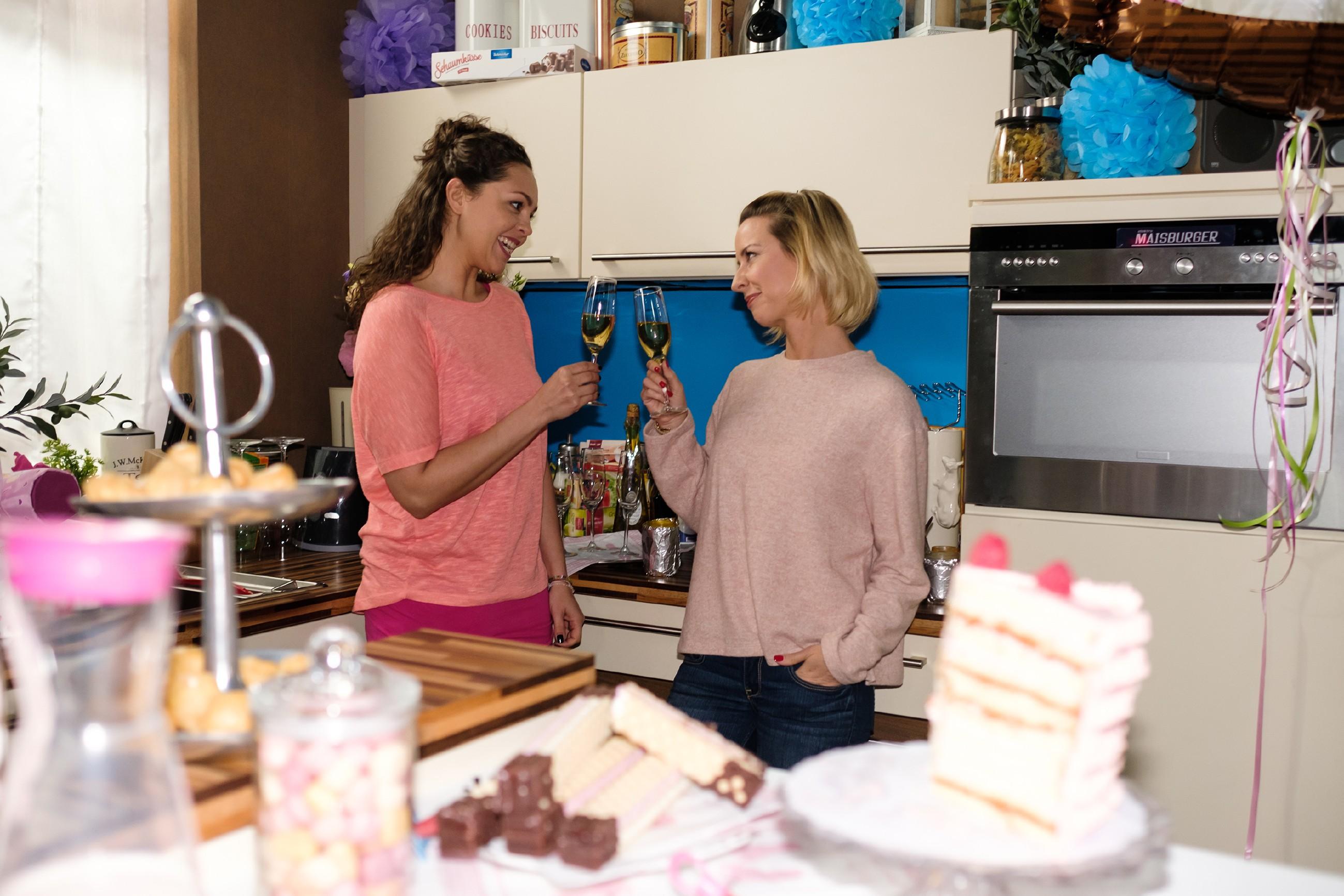 Da Ute (Isabell Hertel, r.) sich nicht um Maja kümmern muss, kann sie ihre Party genießen und stößt mit Caro (Ines Kurenbach) an. (Quelle: RTL / Stefan Behrens)